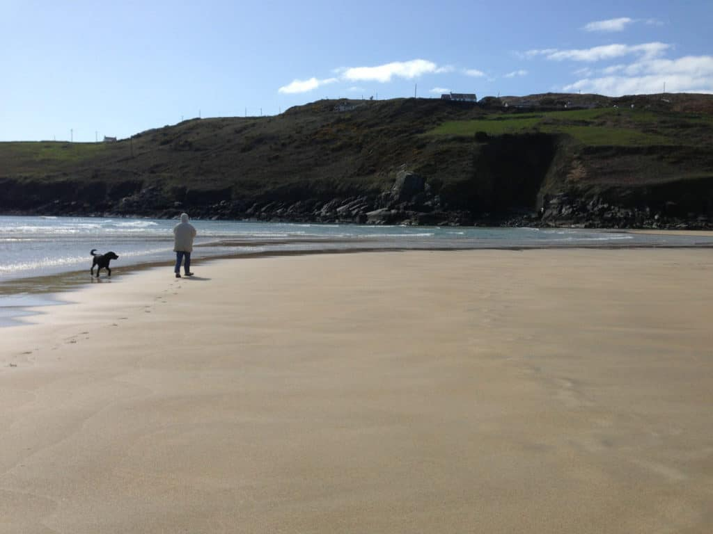 A woman and her black dog walking on a beach